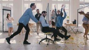 慢动作乐趣不同种族的商务伙伴一起庆祝成功,拍手对在办公室椅子的愉快的男性上司乘驾 股票视频