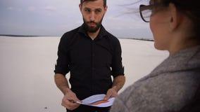 慢动作企业家男性和海滩安排女性谈论的项目在海边 股票录像
