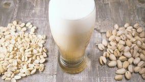 慢动作倒啤酒入一枚玻璃和盐味的坚果在台式视图 股票录像