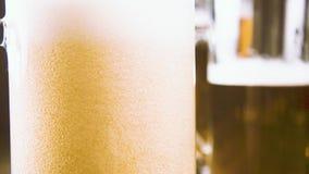 慢动作倒泡沫啤酒入在另一个杯子特写镜头背景的一个杯子  影视素材