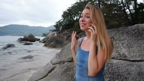 慢动作医科学生女孩谈话在智能手机在海附近 股票视频