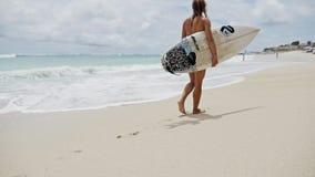 慢动作女孩走的完善的海滩的冲浪板 股票视频