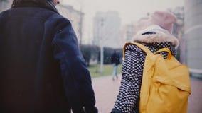 慢动作愉快的微笑的年轻欧洲夫妇在冬天日期,扯拽她的男朋友的女孩一起走由手 股票录像