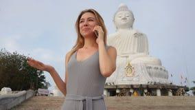 慢动作旅游夫人谈话在智能手机在菩萨附近雕象在泰国 股票录像