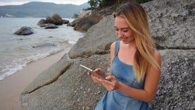 慢动作有片剂的程序员女性有休息在海边 股票录像