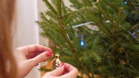 慢动作特写镜头手垂悬在圣诞树的金锥体 影视素材