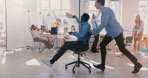 慢动作疯狂的乐趣年轻黑商人骑马办公室椅子,庆祝与队投掷的纸的成功在空气 影视素材