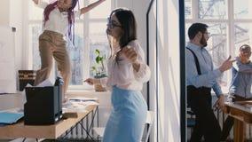慢动作移动式摄影车射击,愉快的不同种族的办公室公司工作者在轻的现代工作场所跳舞,庆祝成 股票视频