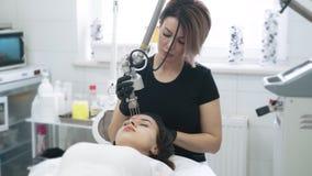 慢动作美容师做妇女的激光面部削皮有特别设备的 影视素材