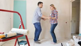 慢动作英尺长度快乐微笑的年轻coupledancing和跳跃,当做在他们新的公寓时的整修 股票视频