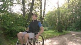 慢动作跟随轮椅的残疾年轻学生人观察自然在他附近,与太阳火光 股票视频