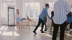 慢动作非裔美国人办公室工作者妇女庆祝事业队促进优胜者椅子乘驾在五彩纸屑下 股票视频