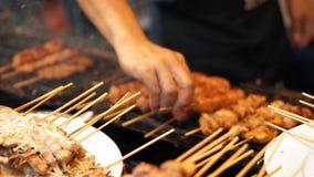 慢动作,可口肉的部分在木串的在一个热的格栅 男性手采取烤肉串 股票录像
