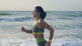慢动作,耳机的美丽的妇女在海岸跑,带领健康生活方式 股票录像