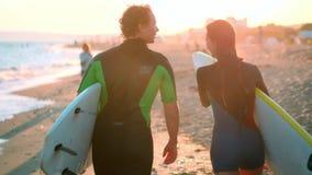 慢动作:人和女孩冲浪者一对年轻夫妇沿在保温潜水服的海滩走 在举行的手上 影视素材