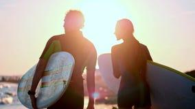 慢动作:人和女孩冲浪者一对年轻夫妇沿在保温潜水服的海滩走 在举行的手上 股票录像