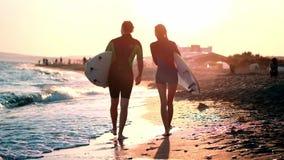慢动作:人和女孩冲浪者一对年轻夫妇沿在保温潜水服的海滩走 在举行的手上 股票视频