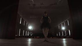 慢动作:在Pointe鞋子的芭蕾舞女演员跳舞在烟的阶段在黑暗的轻的后面看法 照相机在常平架移动 影视素材