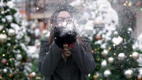 慢动作:年轻女人吹的雪 年轻女人吹的雪 吹在她的雪的逗人喜爱的年轻女人画象 股票视频