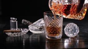 慢动作:从一个蒸馏瓶的倾吐的威士忌酒到翻转者里 影视素材