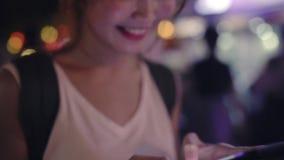 慢动作-亚裔微笑和使用智能手机旅行的单独假日的妇女旅游背包徒步旅行者户外在城市 股票视频