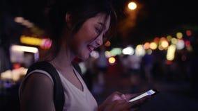 慢动作-亚裔微笑和使用智能手机旅行的单独假日的妇女旅游背包徒步旅行者 股票录像