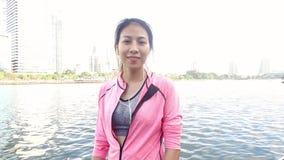 慢动作-健身成套装备的亚裔美丽的妇女使用一smartwatch为听到音乐,谈话在电话 股票视频