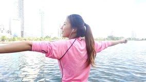 慢动作-健身成套装备的亚裔美丽的妇女使用一smartwatch为听到音乐,谈话在电话 股票录像