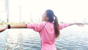 慢动作-健身成套装备的亚裔美丽的妇女使用一smartwatch为听到音乐 股票录像