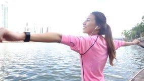 慢动作-健身成套装备的亚裔美丽的妇女使用一smartwatch为听到音乐 股票视频