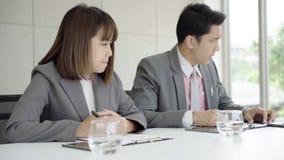 慢动作-商人会议在有他的同事和签的合同工作场所