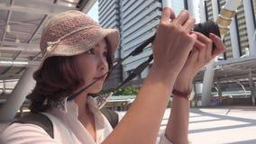 慢动作-快乐的使用照相机的旅客背包徒步旅行者亚裔妇女在街市做照片,当旅行在曼谷时 股票录像