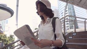 慢动作-快乐的美好的年轻亚洲背包徒步旅行者妇女方向和看在定位图,当旅行曼谷时 股票录像