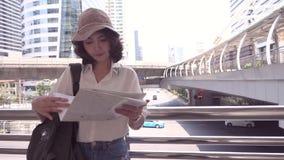 慢动作-快乐的美好的年轻亚洲背包徒步旅行者妇女方向和看在定位图,当旅行曼谷时 影视素材