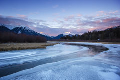 慢慢地流经从高山在日出期间,银朱的湖,班夫国家公园的冷的镇静河结冰的谷,能 库存图片
