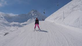慢慢地滑雪下来在山的滑雪倾斜的滑雪者妇女 股票录像