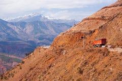 慢慢地移动在红色山路的红色卡车通过云南西部,中国 偏远地区 雪山背景 冬天 免版税图库摄影