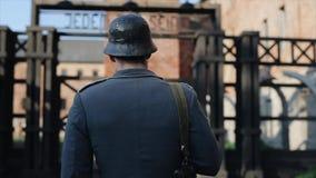 慢慢地走到被弄脏的集中营重建的门的后方接近的观点的德国士兵 ? 股票录像