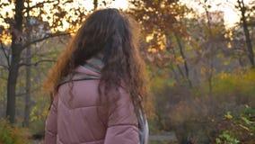 慢慢地走在晴朗的秋季公园和转向照相机的年轻白种人卷发的妇女后视画象  股票录像