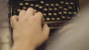 慢慢地键入在有俄国信件特写镜头的老打字机的女性手 在后面后的射击 与罕见一起使用 股票视频