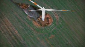 慢慢地飞行在有红旗的,供选择的环境友好的能源运转的风车涡轮上的顶视图寄生虫 股票录像
