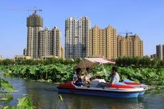 慢慢地驾驶在水中的游船,在公园 免版税库存照片