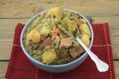 慢煮熟的土豆,青豆,火腿,炖煮的食物 免版税库存照片