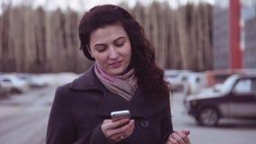 慢的行动 女孩在城市附近走并且使用电话 影视素材
