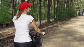 慢的行动 妇女骑马自行车 女性少年骑自行车的循环在晴朗的公园 激活炫耀概念 股票录像