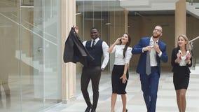 慢的行动 小组确信正面买卖人狂喜赢取 走沿办公室走廊的商人 股票录像