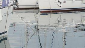 慢的行动 白色游艇在港口,反射在镇静水,蓝色早晨天空中 影视素材
