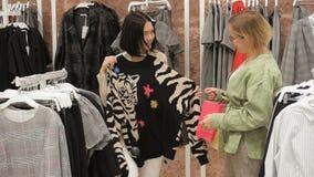 慢的行动 美丽的女孩选择衣裳,谈话并且微笑着,当做购物在精品店时 股票视频