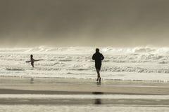 慢跑者和冲浪者,Fistral海滩,北康沃尔 库存照片