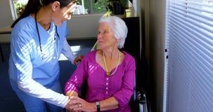 慰问哀伤的残疾资深妇女的白种人女性医生正面图在老人院4k 股票录像